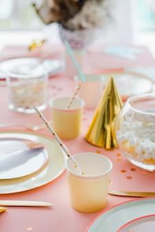 テキスタイルピンクのテーブルクロス、紙のカラフルなカップ、プレートとカクテルストローで子供のパーティーディナーの装飾的なお祝いテーブルの設定。お誕生日おめでとうデコレーション