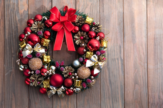 赤と金色のクリスマスのおもちゃの木製テーブルと装飾的なお祝いの花輪
