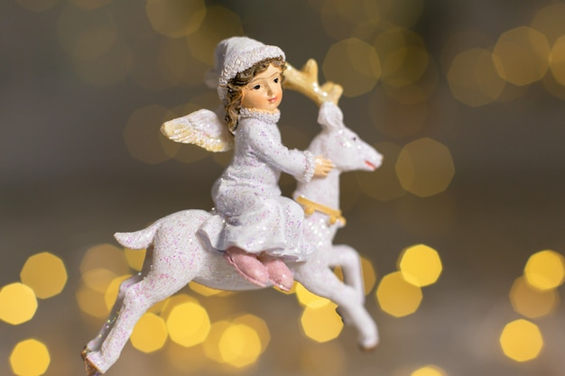Decorative figurines of a christmas theme. figurine of an angel rides on a white deer. christmas tree decoration. festive decor, warm bokeh lights.