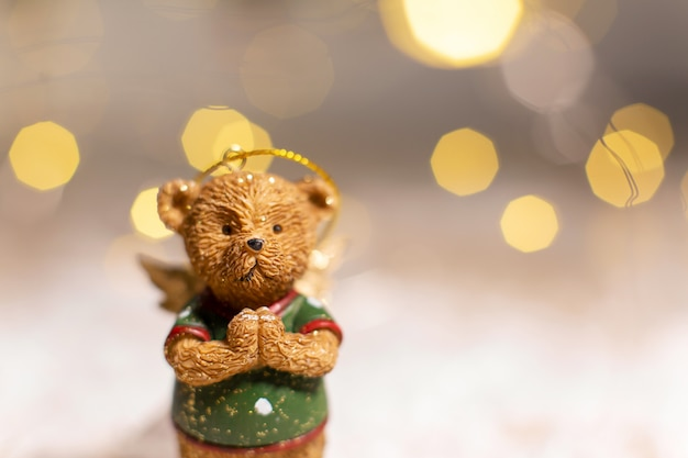 Decorative figurines of a christmas theme. figurine of a cute bear with angel wings. festive decor, warm bokeh lights