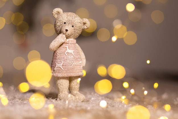 Decorative figurines of a christmas theme. figurine of a cute teddy bear girl in a sweater with deers..