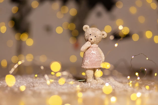 Decorative figurines of a christmas theme. figurine of a cute teddy bear girl in a sweater with deers.