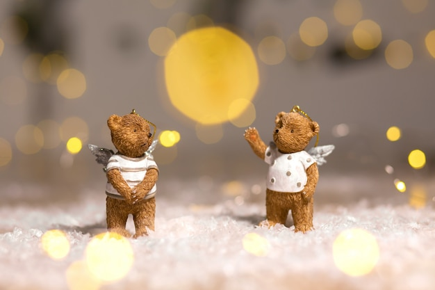 Decorative figurines of a christmas theme. figurines of bears with angel wings. festive decor, warm bokeh lights