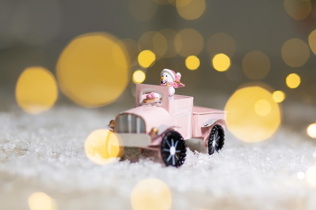 Decorative figurines of a christmas theme. santa statuette rides on a toy car with a trailer for gifts.