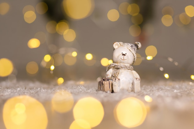 Decorative figurines of a christmas theme. statuette of a teddy bear with a scarf, sit next to the box with a christmas present.