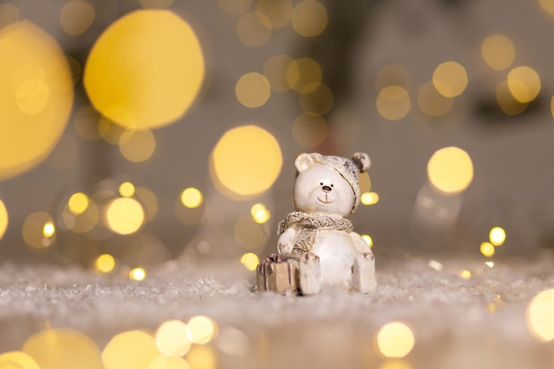 Decorative figurines of a christmas theme. statuette of a teddy bear with a scarf, sit next to the box with a christmas present