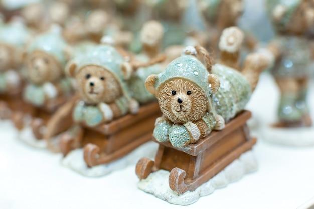 Decorative figurines of a christmas theme. statuette of a teddy bear on a wooden sleigh. christmas tree decoration. festive decor, warm bokeh lights.