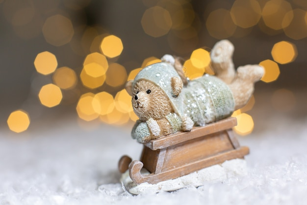 Decorative figurines of a christmas theme. statuette of a teddy bear on a wooden sleigh.