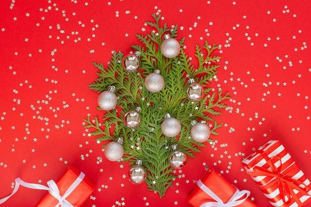 크리스마스 공이 있는 thuja 나뭇가지로 만든 장식용 전나무, 반짝이는 은색 별이 있는 빨간색 배경에 선물 상자, 휴일 배경