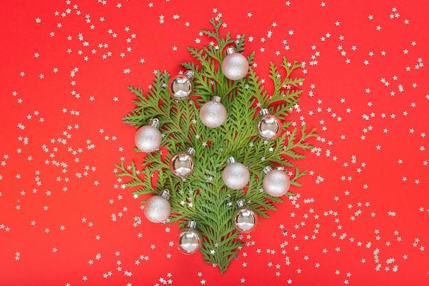 은색 반짝이 별, 휴일 배경이 있는 빨간색 배경에 크리스마스 공이 있는 thuja 나뭇가지로 만든 장식용 전나무