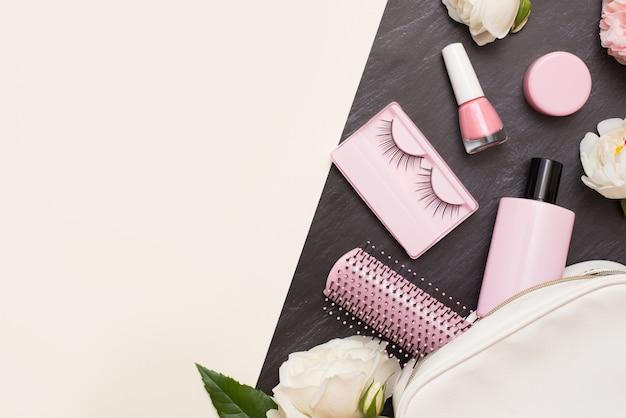 化粧品と花を使った装飾的なフラットレイコンポジション