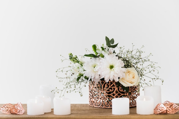 Decorative flower vase with white candles on wooden table against white background