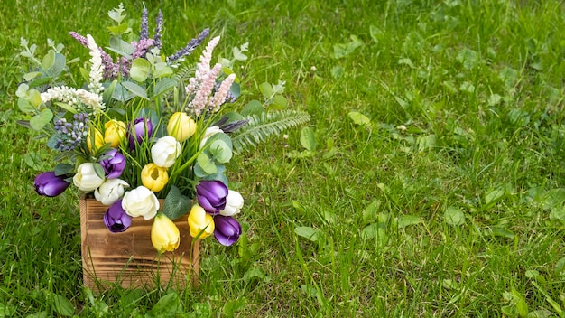 Decorative flowers in a wooden box on a green grass. copy space