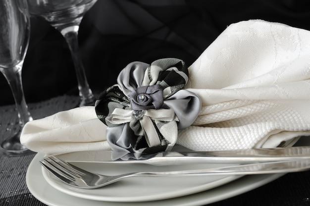 칼 붙이와 함께 접시에 꽃 모양의 클램프와 장식 접힌 냅킨