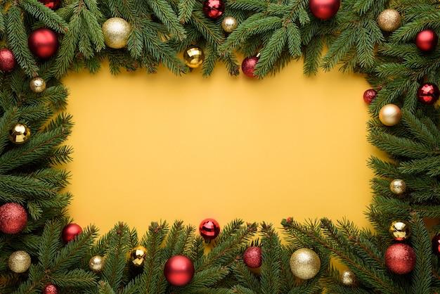 クリスマスボールとモミの枝の装飾的なフレーム。クリスマスと新年のデザインの黄色の背景。プロモーション、広告、おめでとうテキスト用のコピースペース
