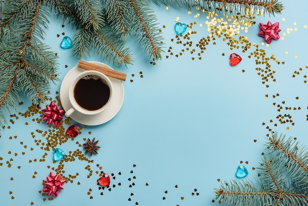 Decorative frame with fir branches, decorations, tinsel, bows and a cup of coffee with cinnamon. christmas composition with copy space on a blue background.