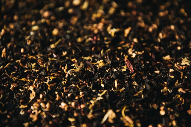 Decorative full frame image of dry green and black tea h fruit and flower additives selective focus