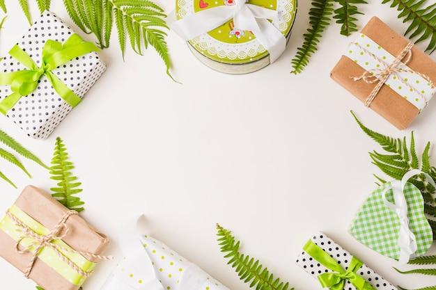 Декоративные подарочные коробки и листья ветки расположены на белом фоне