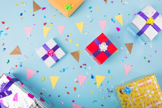Decorative gift boxes with bunting flag and confetti over the blue background