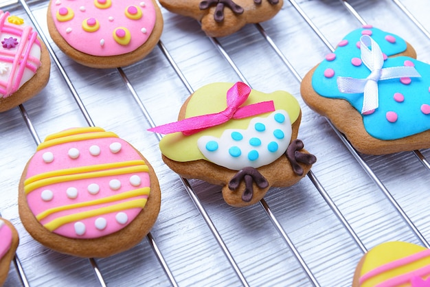 Decorative gingerbread easter cookies on baking wire rack and white wooden table