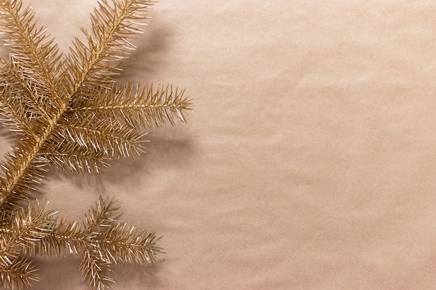 Decorative golden christmas tree twig on craft paper