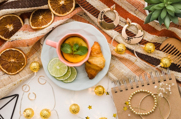 Decorative golden lights with female accessories and tea cup on white backdrop