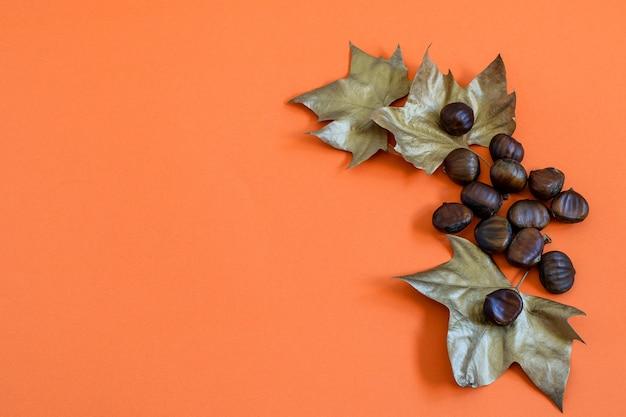 Декоративные золотые кленовые листья и каштаны на оранжевом бумажном фоне хорошая рамка для хэллоуина или приглашение на вечеринку