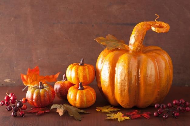 Декоративная золотая папье-маше тыква и осенние листья на хэллоуин