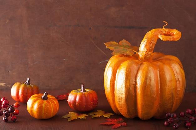 Decorative golden papier-mache pumpkin and autumn leaves for halloween thanksgiving