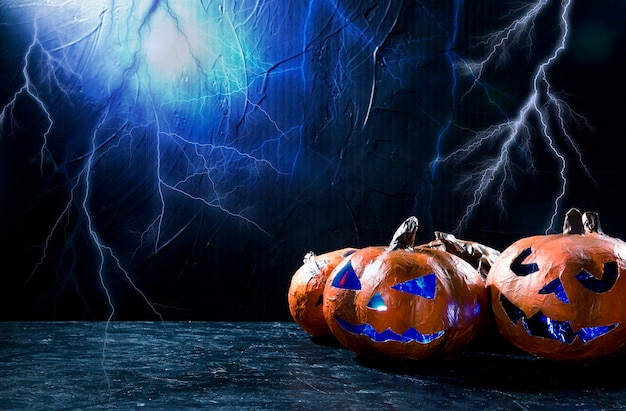 Decorative halloween pumpkin with carved faces and lightning on background