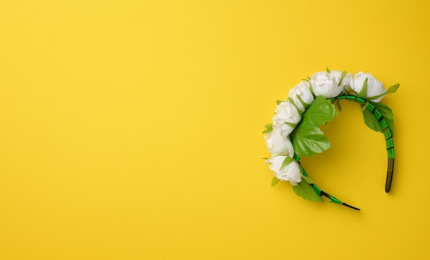 Decorative headdress hoop with white roses on a yellow background. wreath for costume