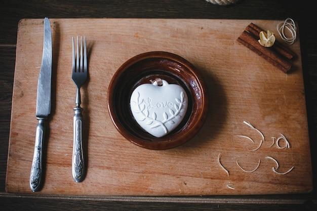Cuore decorativo accanto a una forchetta e coltello