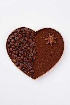 Декоративное сердце из кофейных зерен и растворимого кофе. изолированные на белой поверхности