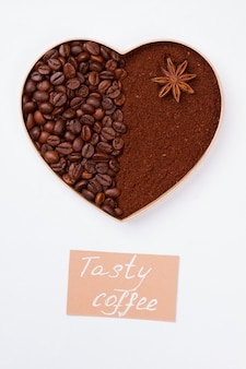 Декоративное сердце из кофейных зерен и пудры с анисом. изолированные на белой поверхности