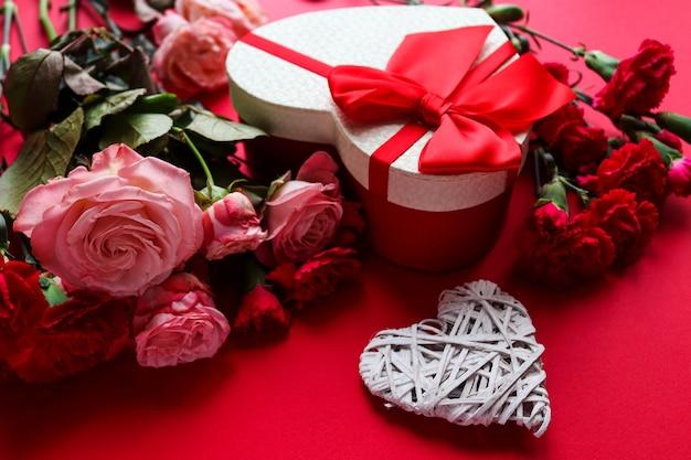 装飾的なハート、ハート型のギフトボックス、赤い背景のクローズアップの花。