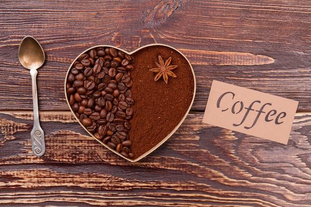 Декоративное сердце из кофейных зерен и порошка растворимого кофе. деревенская деревянная поверхность.