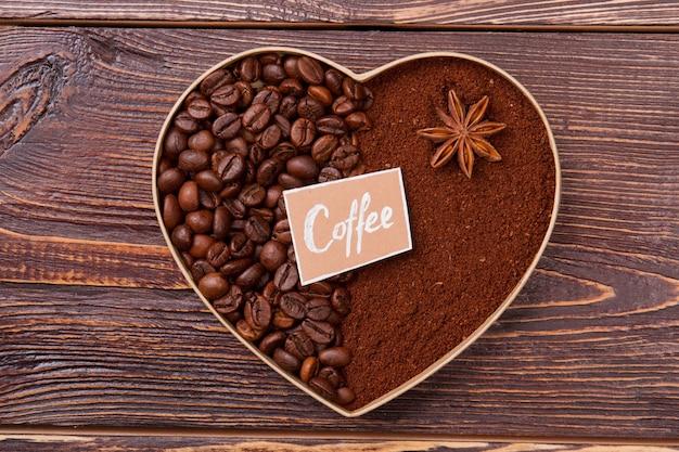 Декоративное сердце из кофейных зерен на дереве. символ любви кофейных зерен и растворимого кофе.