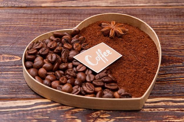 커피 알갱이로 만든 장식 심장. 아니스와 인스턴트 커피 분말. 소박한 목재 표면.