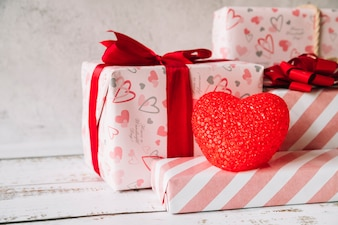 Decorative heart near heap of gift boxes in wrap