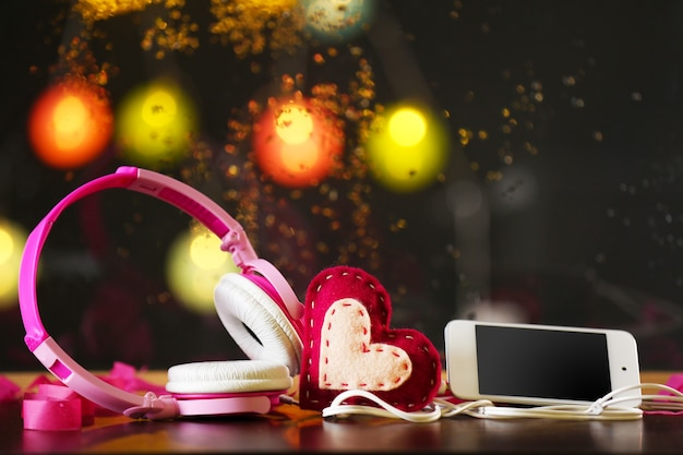 Декоративное сердце с наушниками и мобильным телефоном на фоне огней