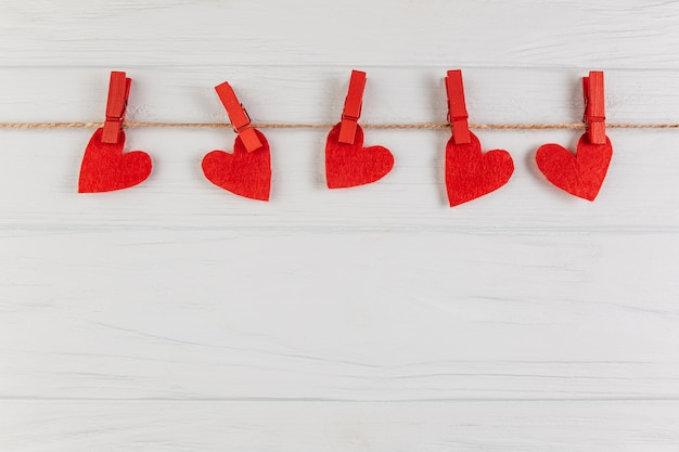 Decorative hearts hanging on rope with pegs