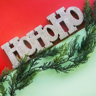 Decorative ho ho ho title near arborvitae twig