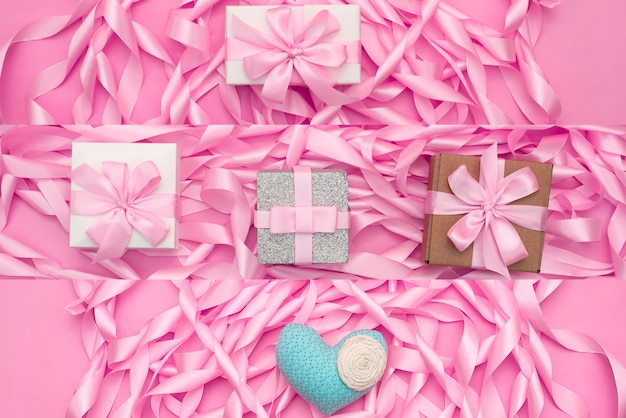 Decorative holiday gift boxes with pink color on pink background.