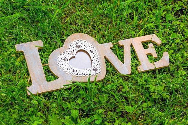 緑の草の上の木の文字の装飾的な碑文の愛