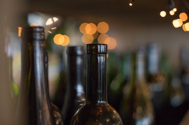 Decorative interior elements-dark glass empty bottles on shiny background.