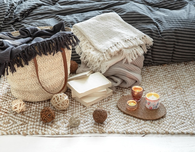 Oggetti decorativi in un accogliente interno di casa con grande borsa di paglia di vimini ed elementi decorativi.