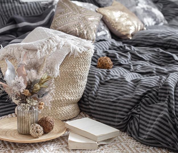 居心地の良い家のインテリアの装飾品。籐のわらの大きなバッグ、そして装飾的な要素。スタイルと快適さのコンセプト。