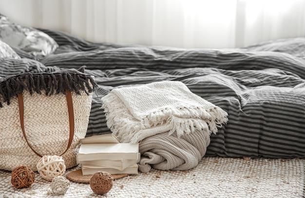籐のわらの大きなバッグと装飾的な要素を備えた居心地の良い家のインテリアの装飾品。