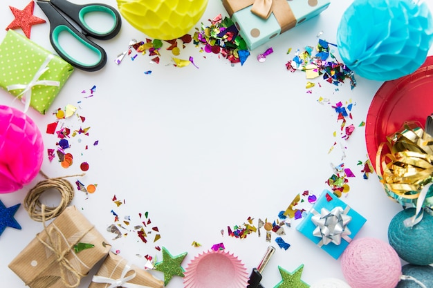 Decorative items; scissor; gift boxes; cupcake holder and confetti against white background