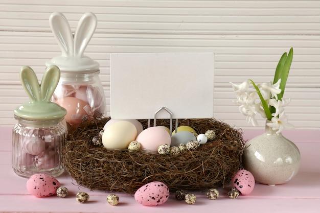 バニーの耳のイースターエッグ、ホワイトボード、白い木製の背景にピンクのテーブルにカラフルな卵ヒヤシンスの花と装飾的な巣の装飾的な瓶